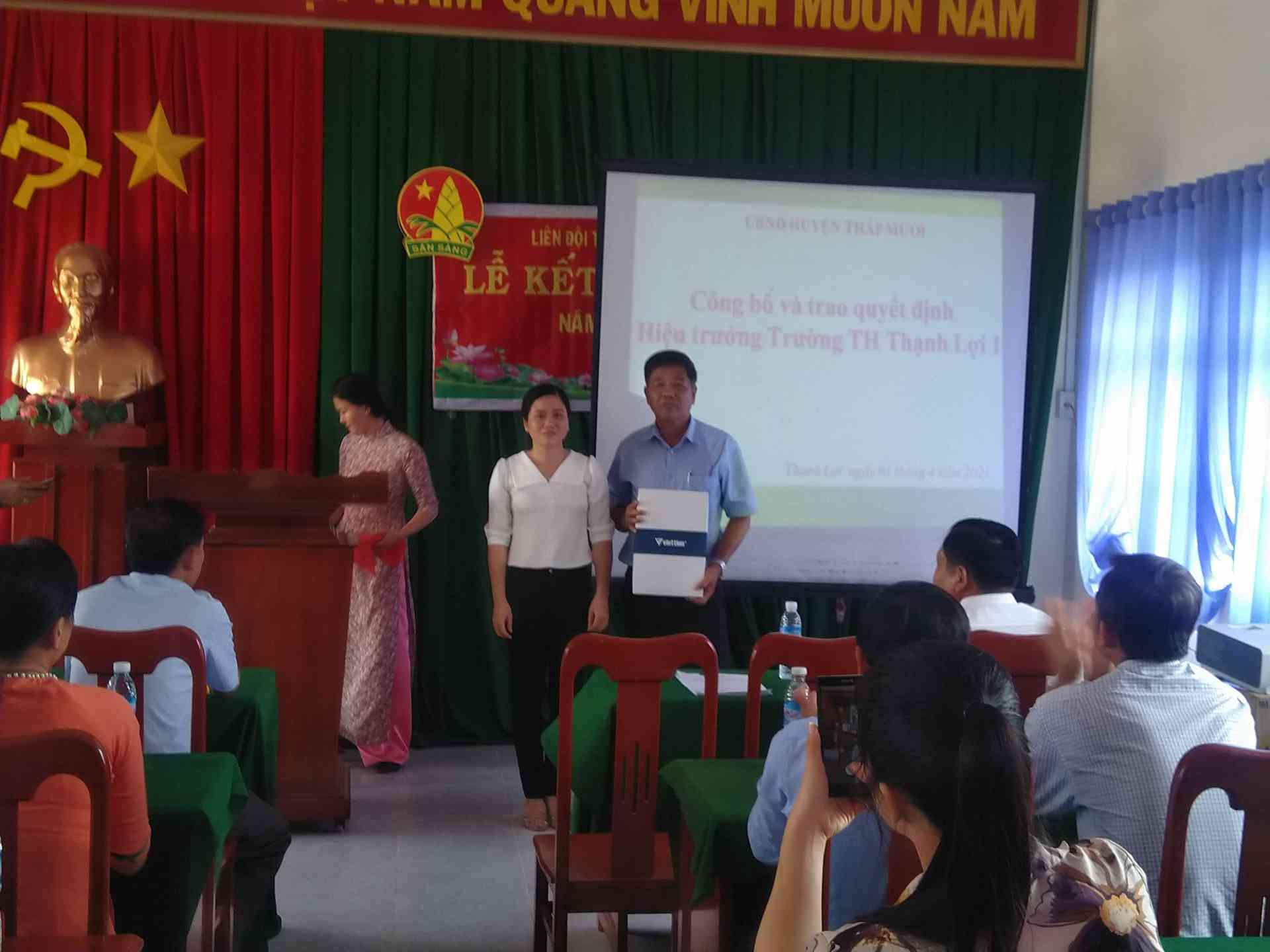 Cô Nguyễn Thị Mỹ Hạnh - phó hiệu trưởng nhà trường lên trao món quà lưu niệm cho thầt Nguyễn Thành Tâm.